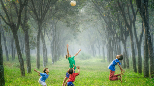 children playing outdoors jumping and reaching for a ball